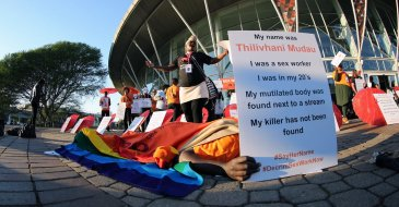 Photographer: International AIDS Society/Abhi Indrarajan. Caption: Activists protest the criminalisation of sex work outside the 21st International AIDS Conference in Durban, South Africa.